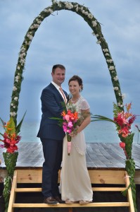 The lovely bride and groom underneath the wedding arch overlooking the Caribbean Sea.